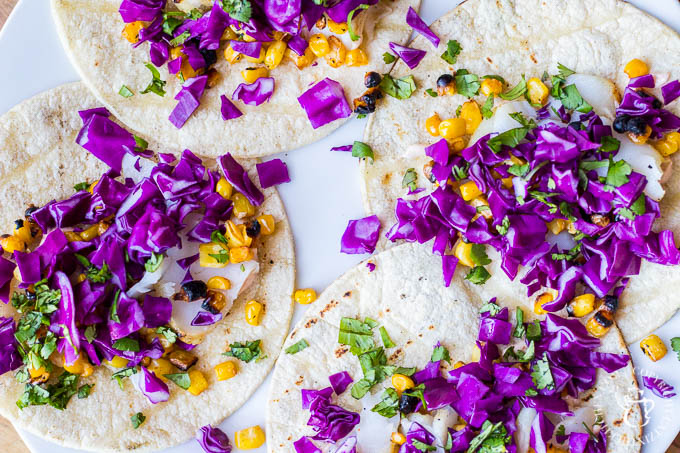 Top the tortillas conservatively with the flaked fish, and then add corn, red cabbage, cilantro and garnish with lime wedges. That's it - time to eat!
